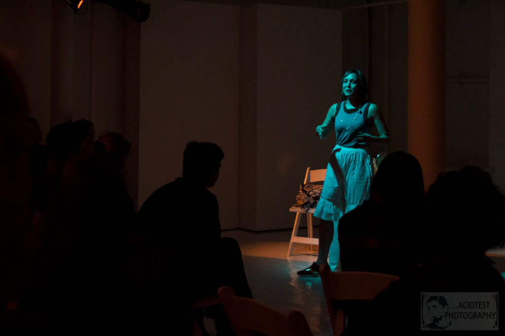 Woman performs play in blue light.