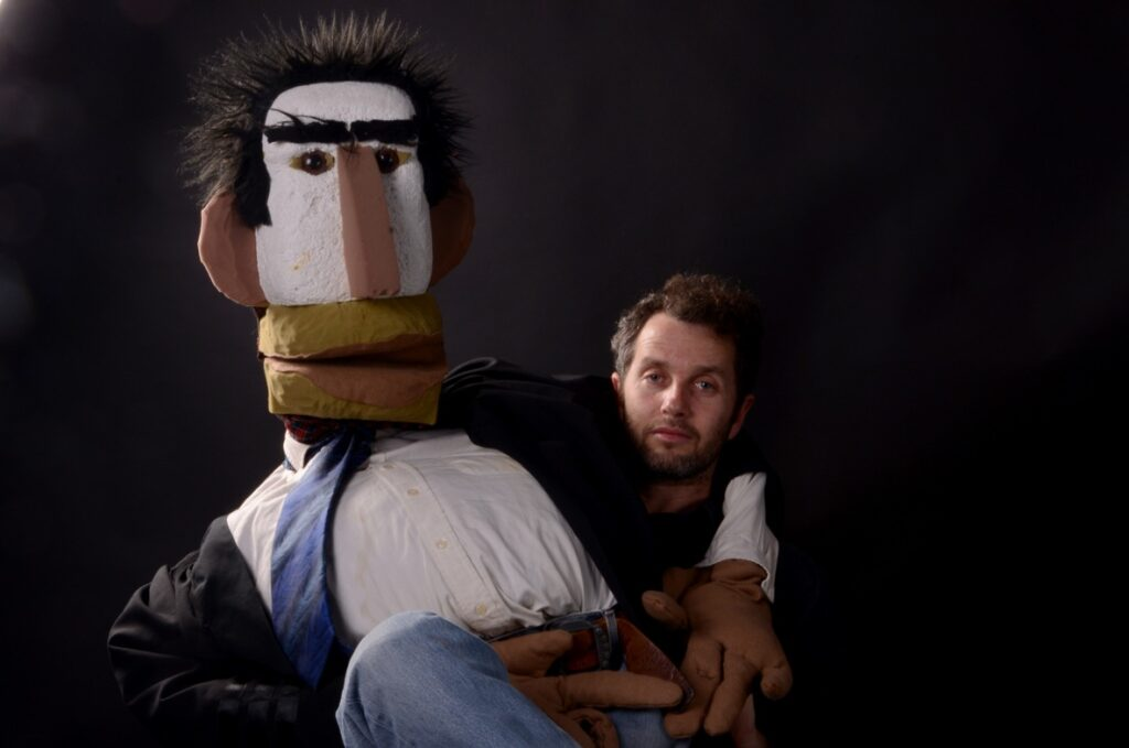 Man holding a giant puppet