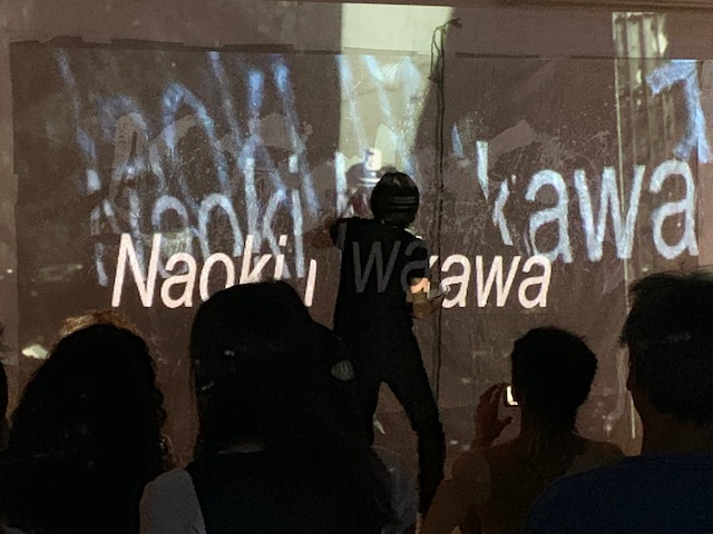 Man paints a canvas while an image is projected on it. Audience watches